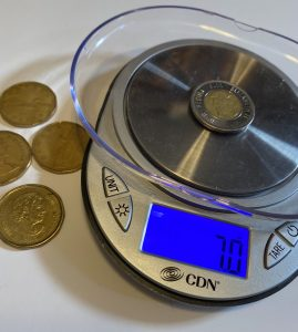 coins on a yarn scale to check accuracy