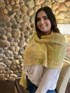 woman wearing knitted Going Postal Wrap in front of stone wall