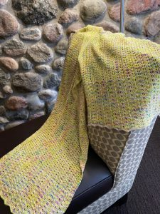 Goiong Postal Wrap (a knitted shawl) draped on a chair