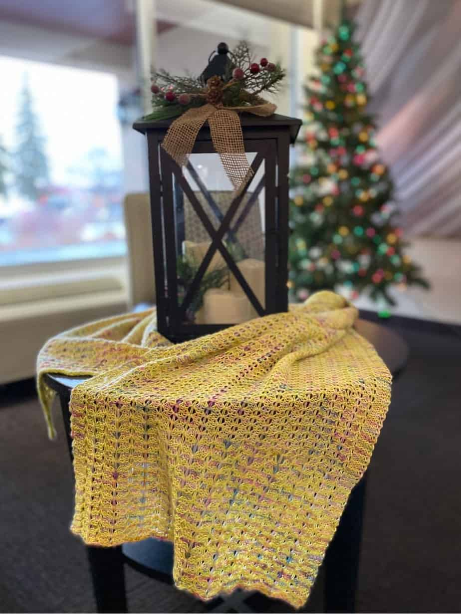 Goiong Postal Wrap (a knitted shawl) laying on a table with Christmas decorations