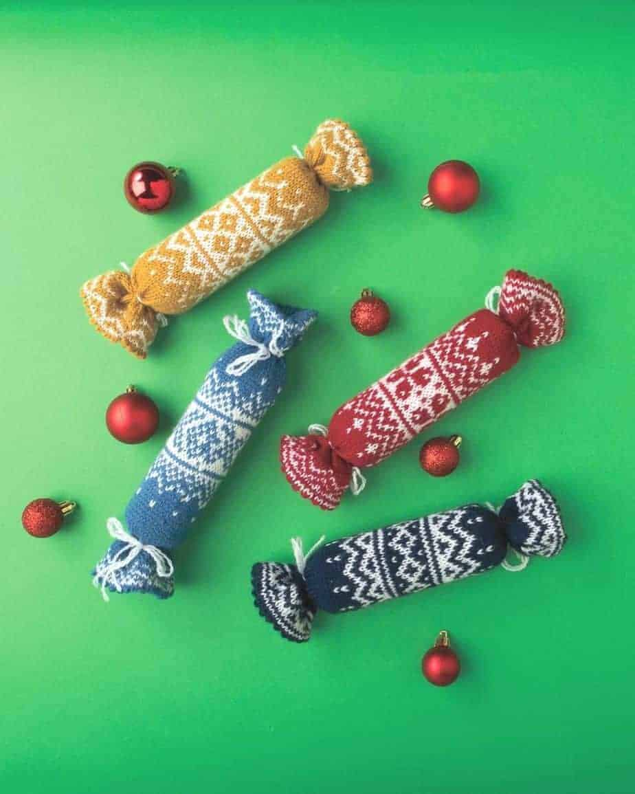 Knitted Norwegian Chrsitmas Crackers on green background with baubles