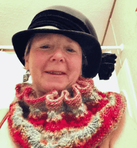 Woman wearing a colourful knitted lace cowl and black hat.