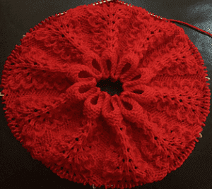 A red knitted lace Plumed Cowl on the needles being knit in the round.