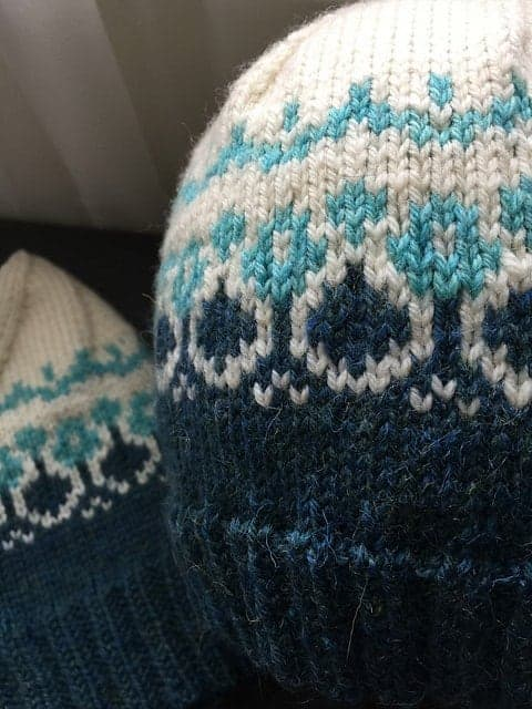 A close up of two blue and white stranded knit hats.