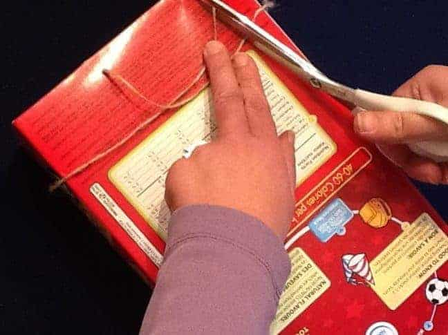 A hand wrapping string around the form to measure handles. for the recycled newspaper gift bag.