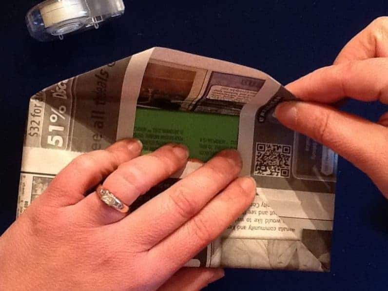 A hand folding newspaper over the bottom of the box.