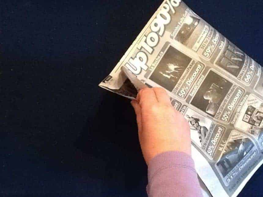 A hand holding the two edges of a newspaper together.
