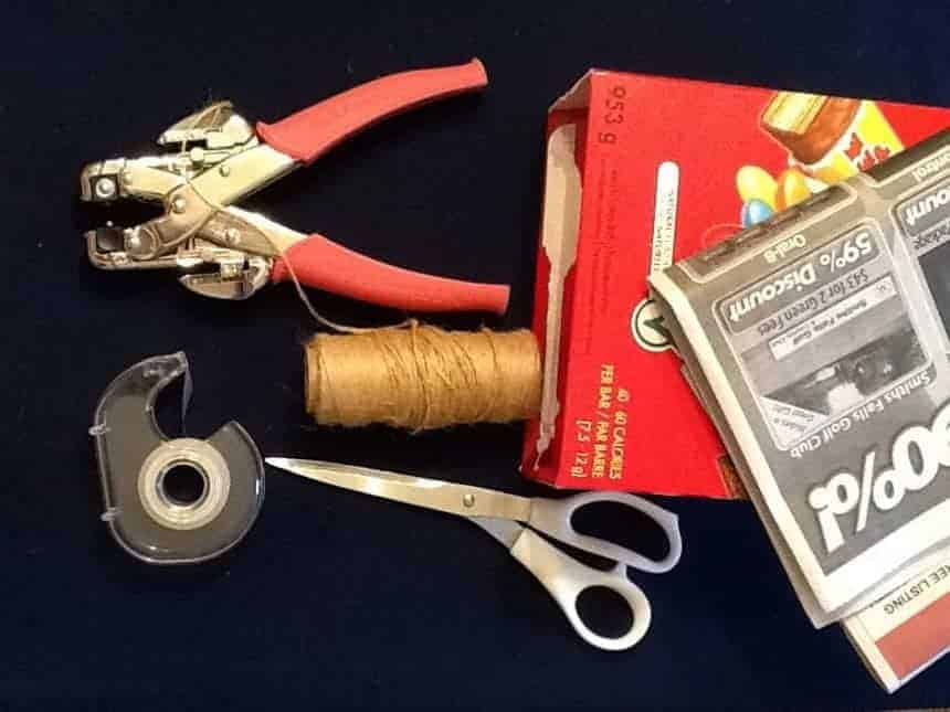 An image of the materials required to make a recycled newspaper bag: newspaper or flyers, box, invisible tape, hole punch, string and scissors