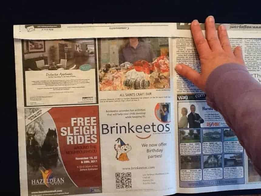 A hand folding the top of a piece of newspaper over by 3/4