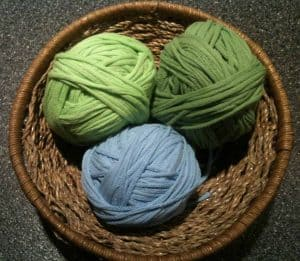 Two green and one blue ball of t-shirt yarn n a wicker bowl