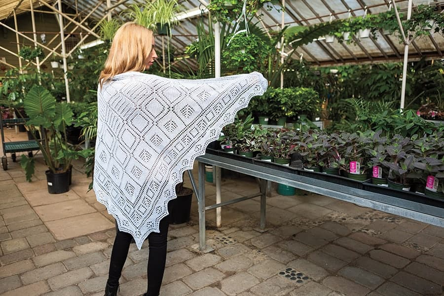 A model in a green. house wearing the Shetland Mosaic Shawl – A knit shawl with various lace diamonds