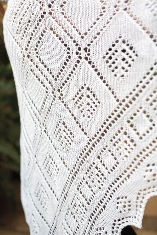 A close-up of the Shetland Mosaic Shawl – A knit shawl with various lace diamonds