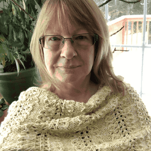 A woman wearing a beautiful, knitted pale yellow lace cowl/cape,